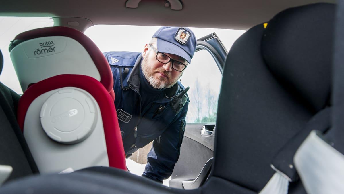 Poliisi katsomassa turvaistuimia.