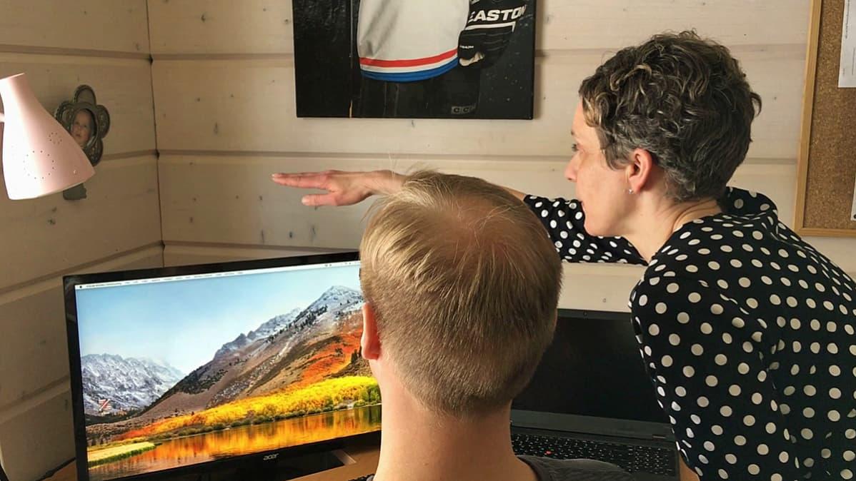 Työterveyslaitoksen Erja Sormunen opastaa Juha-Matti Jääskelälle näyttöpäätteen oikeaa korkeutta.