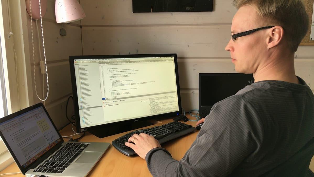 Juha-Matti Jääskelä käyttää tietokonetta kotinsa työpisteellä.