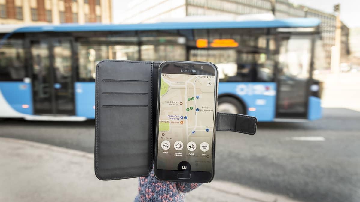 Whim-mobiilisovellus älypuhelimen näytöllä, taustalla linja-auto.