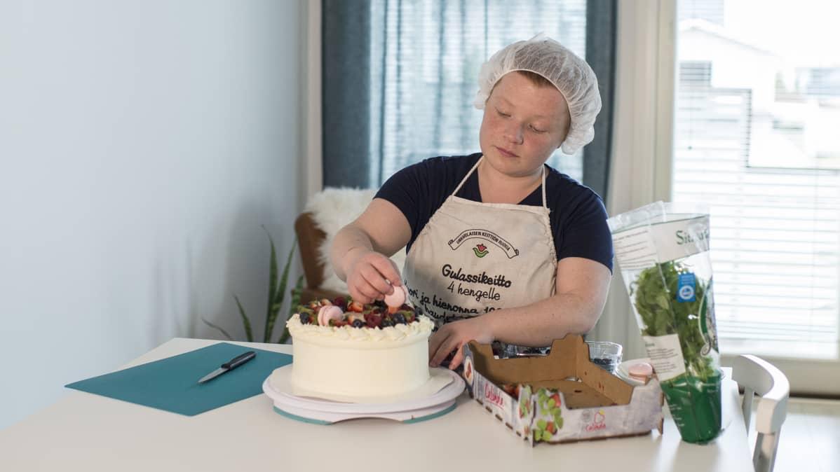 Ruusa-Mari Höyhtyä koristelee kakkua.