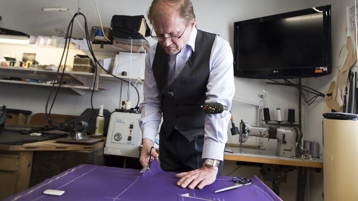 Vaatturimestari Matti Hampaala leikkaa kangasta.