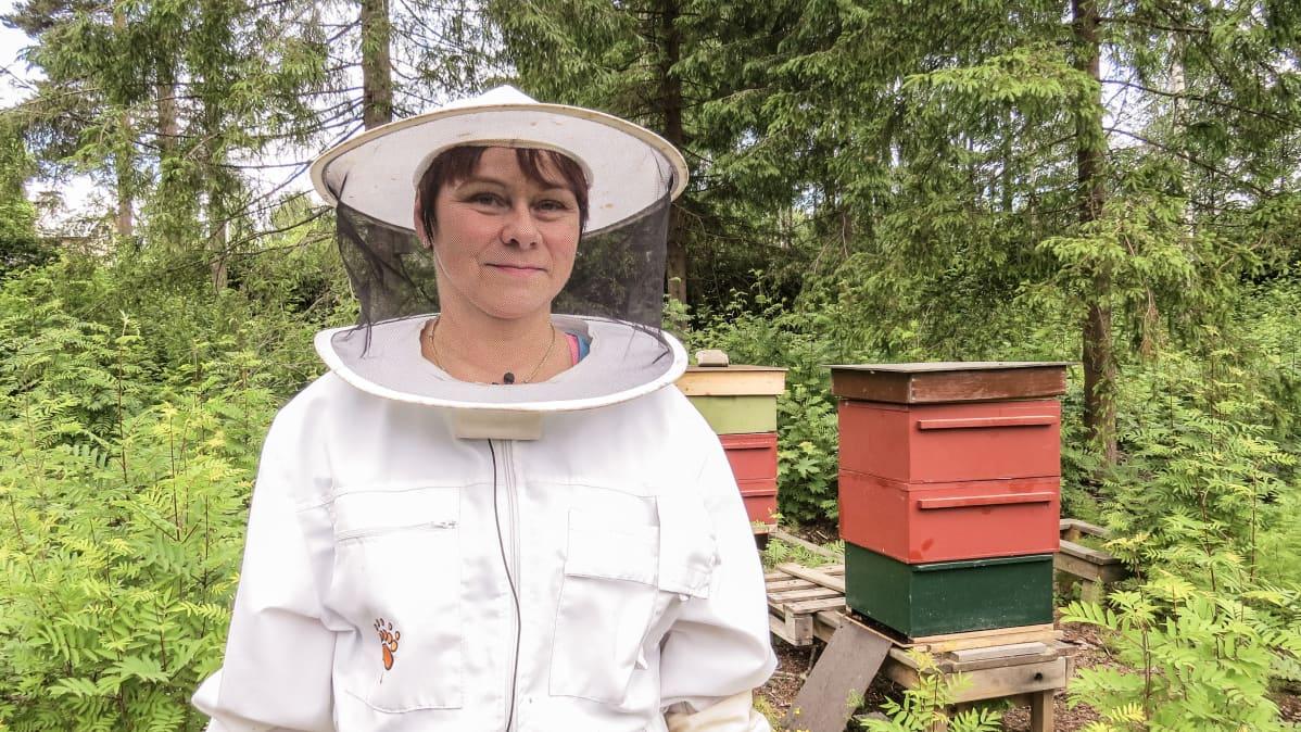 Katriina Laukkanen mehiläispesän lähellä.
