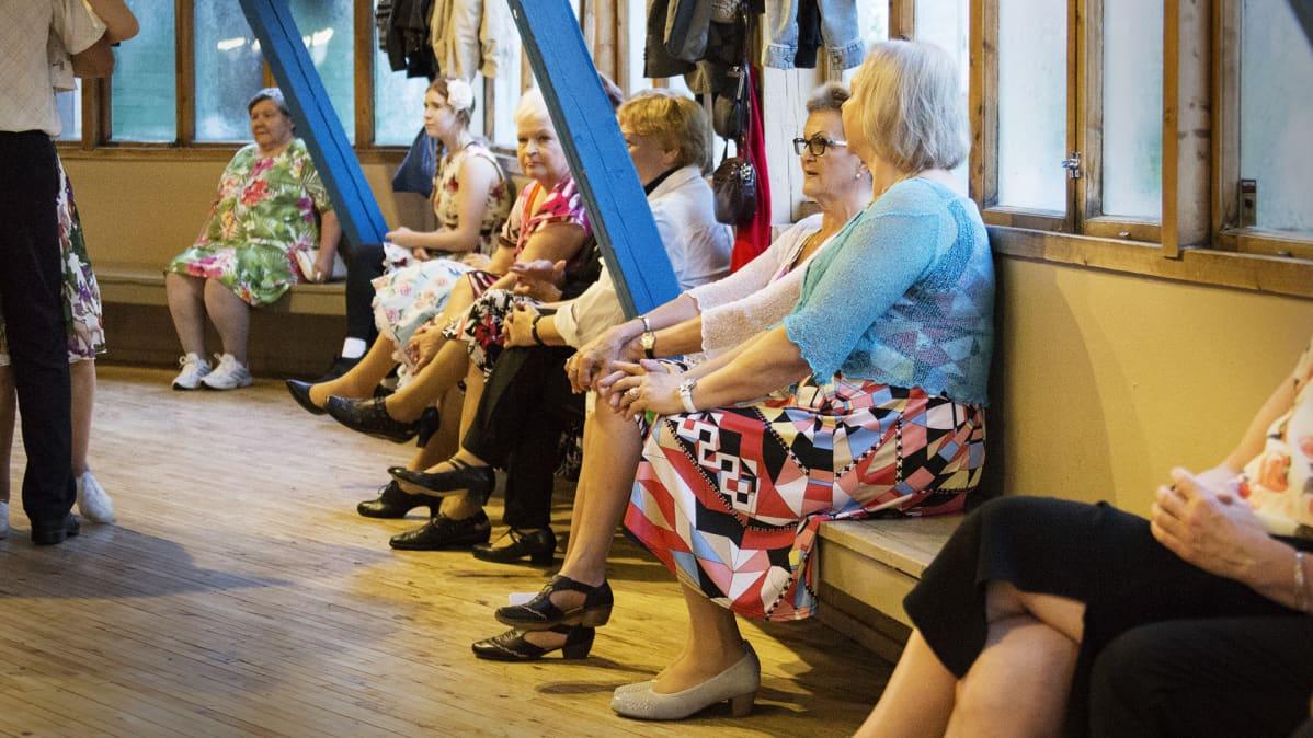 Naisia istumassa tanssilavan penkeillä.