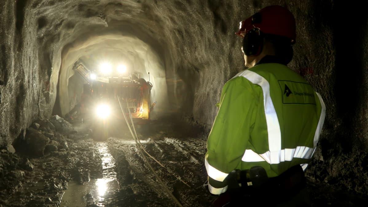Mies ja kaivoskone kaivoskäytävässä