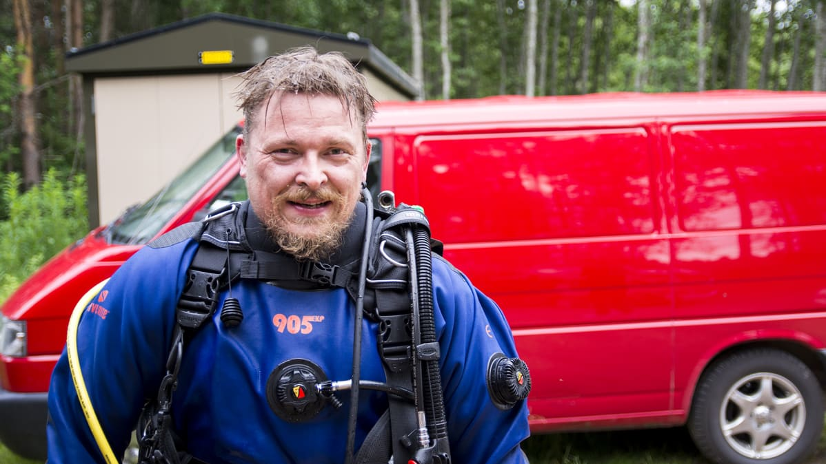 Tero Möttönen katsoo kameraa sukelluspuku päällään.