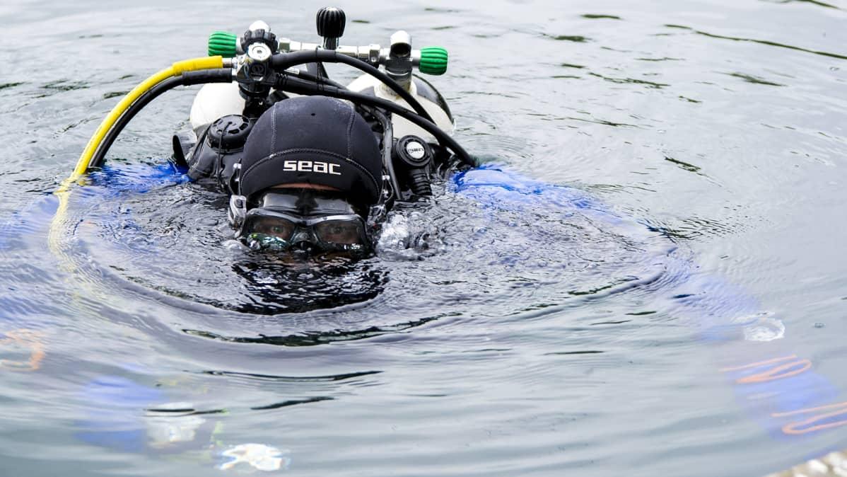 Tero Möttönen sukellusvälineineen osittain pinnan alla.