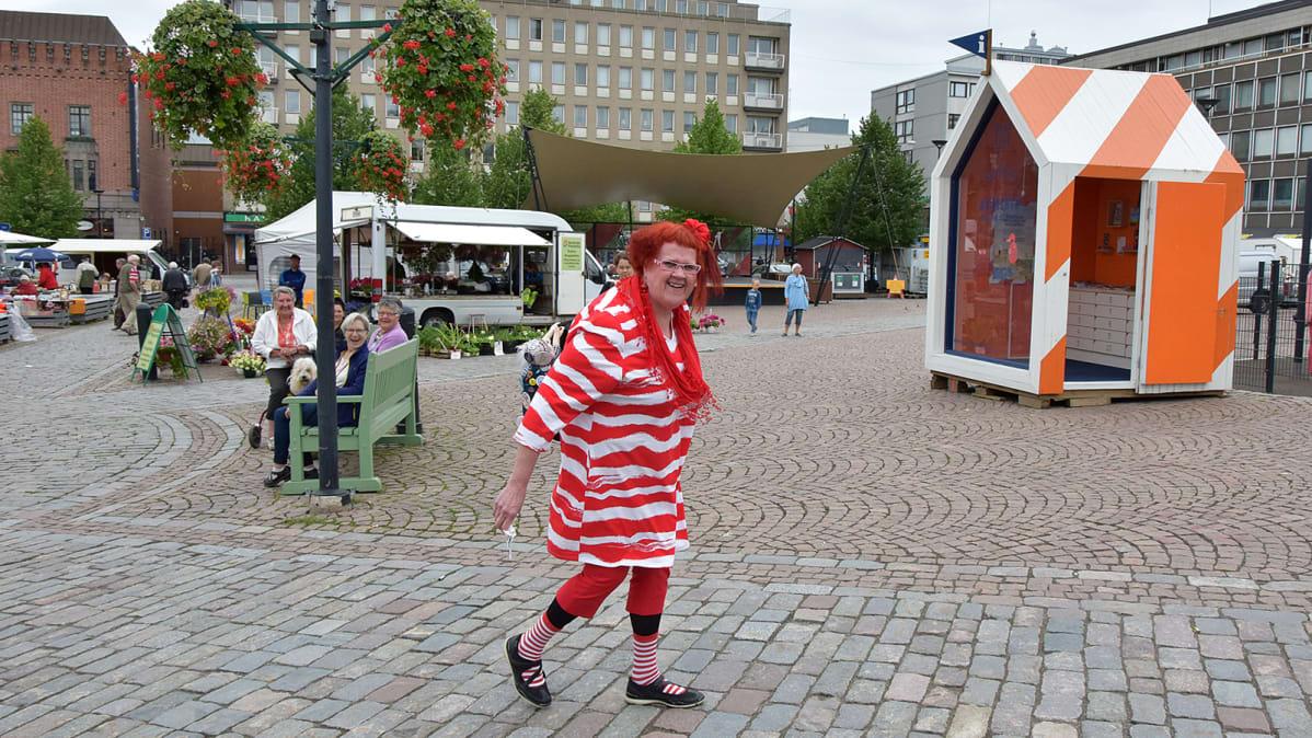 Punavalkoiseen asuun pukeutunut nainen kävelee Hämeenlinnan torilla