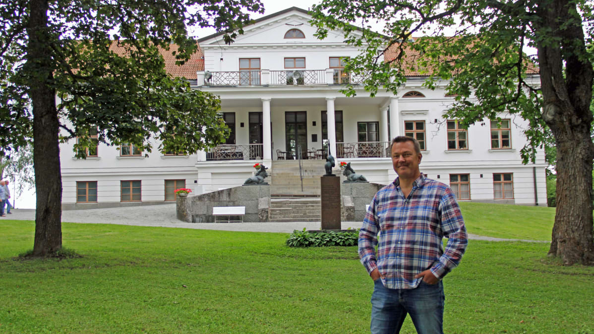 Laukon kartanon isäntä Jouni Minkkinen seisoo kartanon päärakennuksen edessä