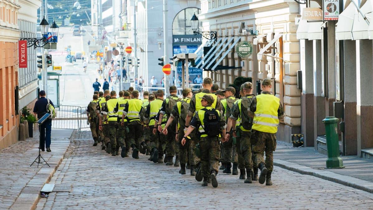 Sotilaspoliisit kävelevät presidentinlinnan läheisyydessä Helsingissä.