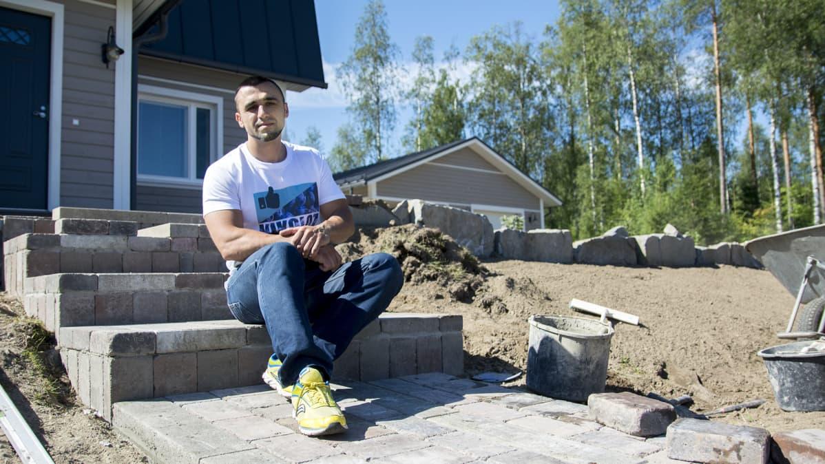 Nikoloz Dzutsovia istuu talon portailla. Taloon ollaan rakentamassa kivetys.