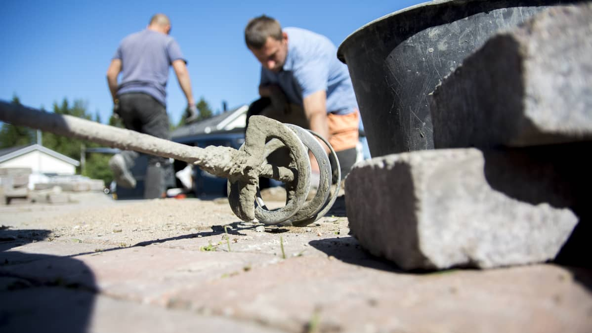 Etualalla työkaluja. Taustalla sumeana kaksi ukrainalaista työntekijää rakentamassa katukivetystä.