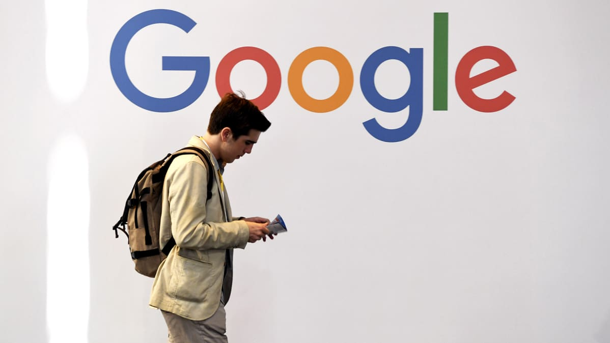Mies kävelee Googlen logon edessä.