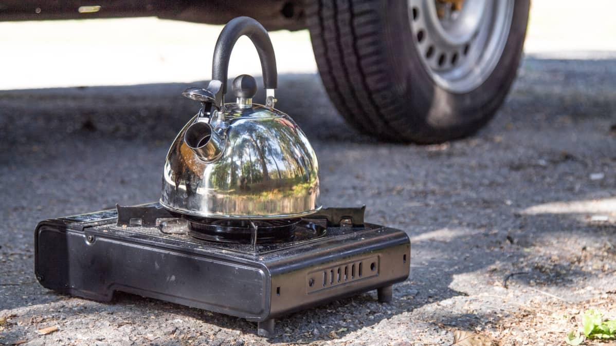 Kaasukeittolevy matkapakettiauton edustalla