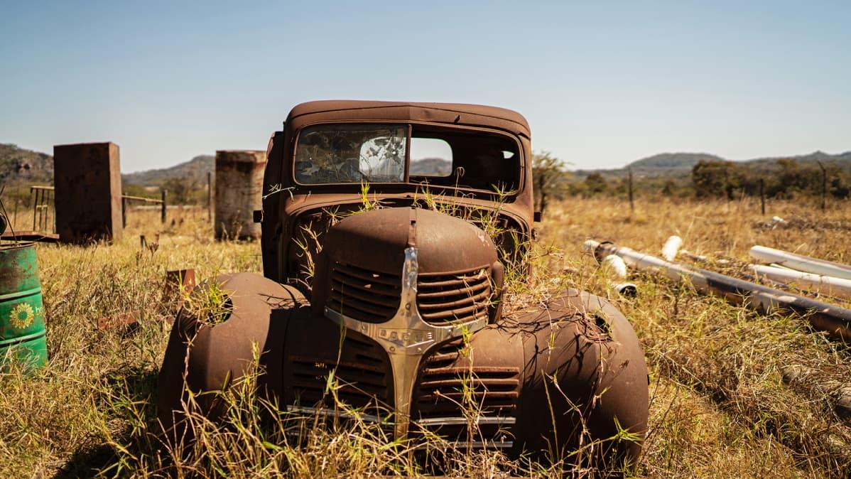 Hylätty auto pellolla.