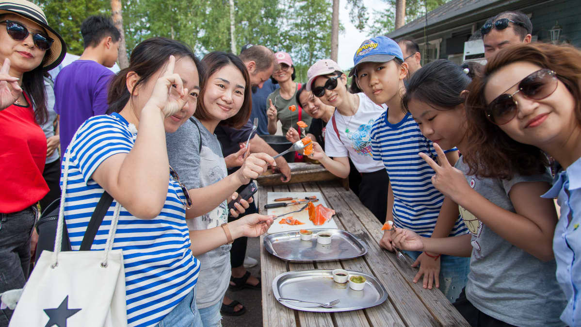 Kiinalaiset turistit nauttivat tuoreesta lohesta Imatran Vuoksen kalastuspuistossa
