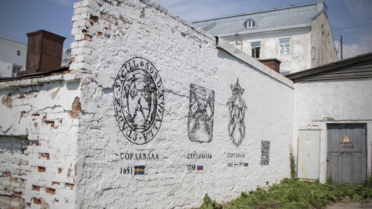Vaakunoita ja vuosilukuja seinässä.