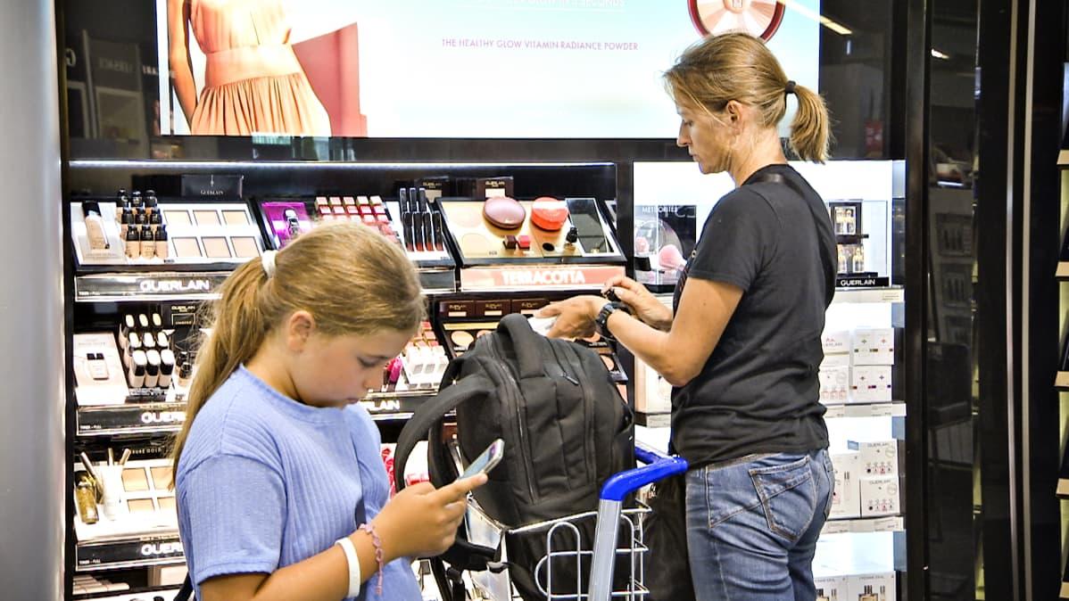 Äiti ja lapsi kosmetiikkaostoksilla Helsinki-Vantaan lentoasemalla.