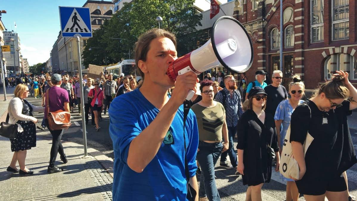 Mies puhuu kovaääniseen Turku ilman natseja -mielenosoituksessa.