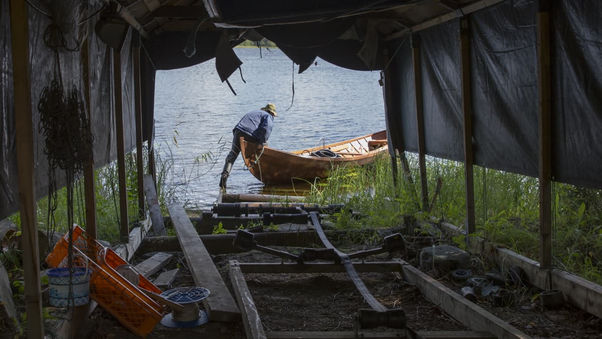Mies työntää venettä vesille.