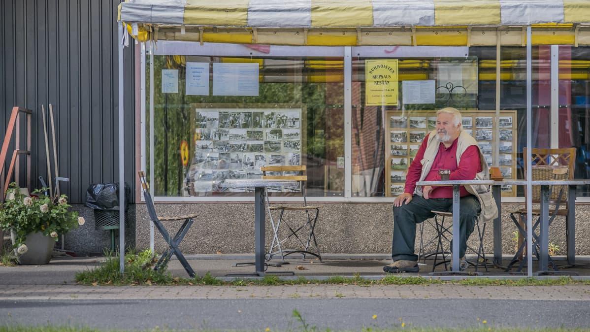 Mies istuu baarin edessä.