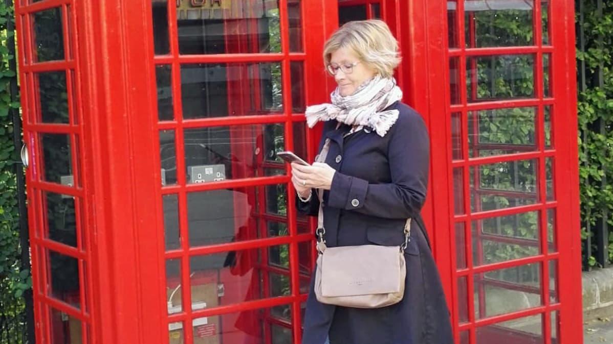 Nainen seisoo englantilaisen puhelinkopin edessä.