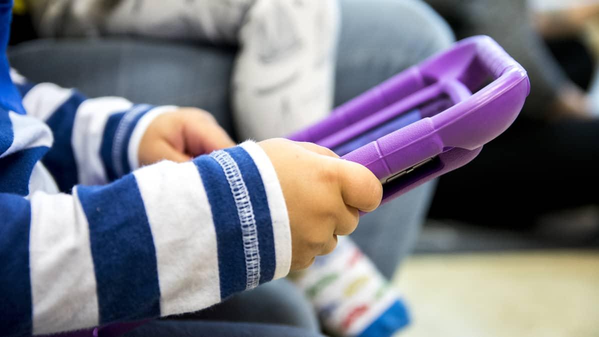 Lapsen kädet pitelevät tablettia.