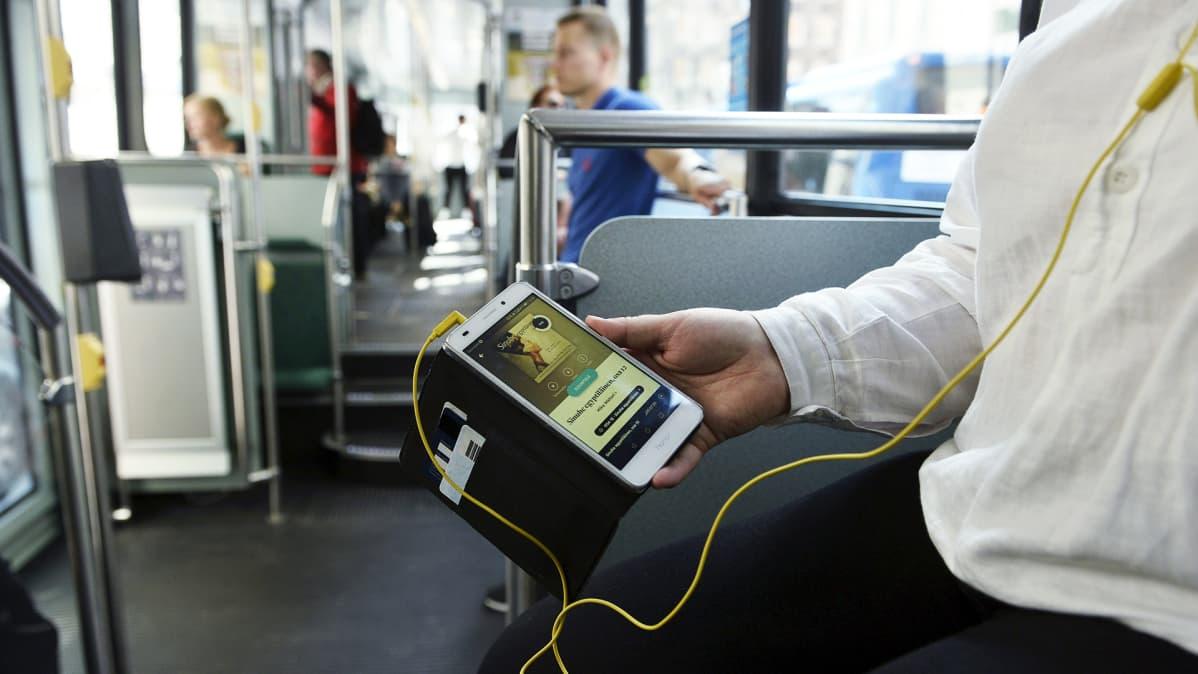 ÄÄnikirjan kuuntelua raitiovaunussa.