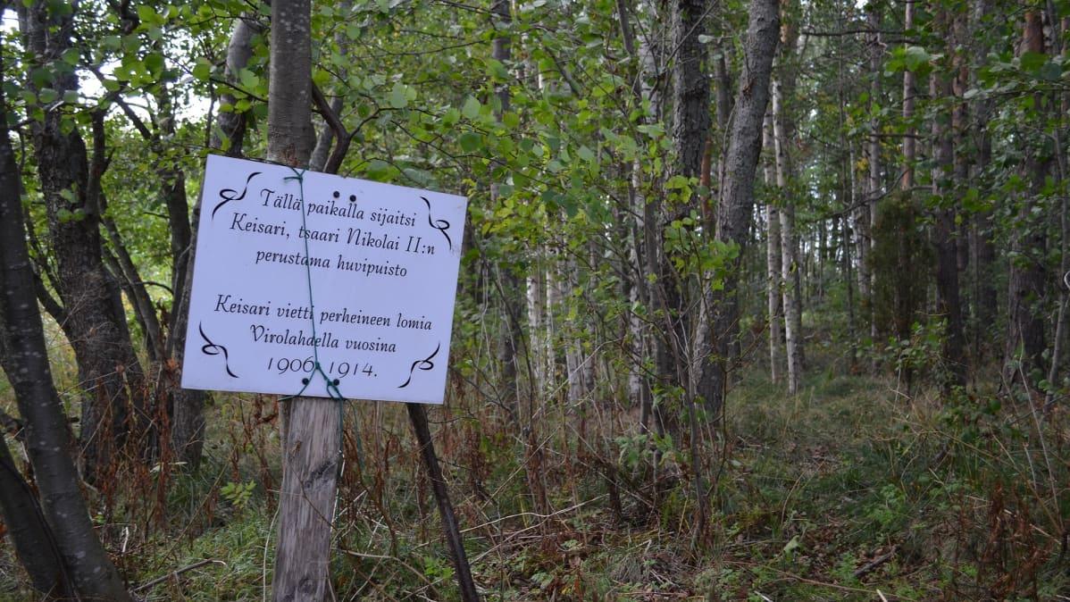 Valkoinen kyltti metsässä. Kyltissä kerrotaan paikalla sijainneen keisari, tsaari Nikolai II:n perustama huvipuisto.