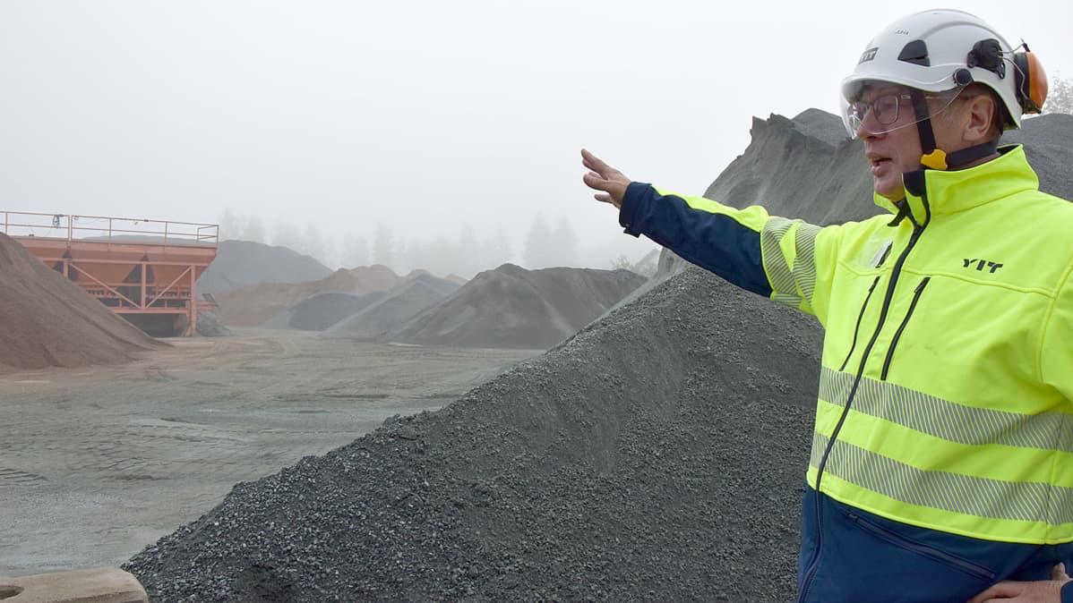 Kypäräpäinen mies osoittaa kädellä asfalttiaseman kiviaineskasoja