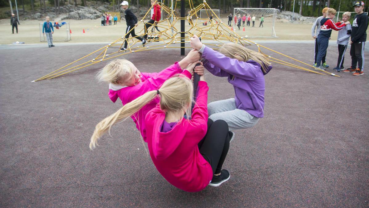 Kolme tyttöä pyörii koulun pihalla olevassa leikkitelineessä vauhdikkaasti.