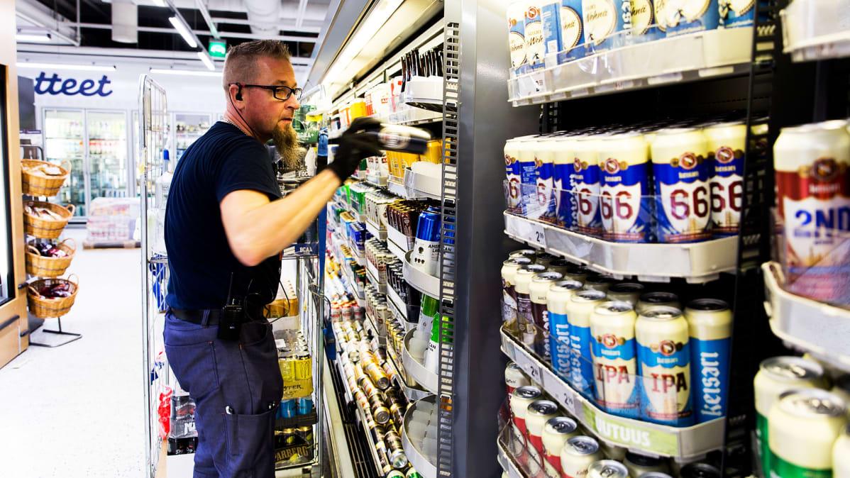 työntekijä täyttää kaupan juomahyllyä.