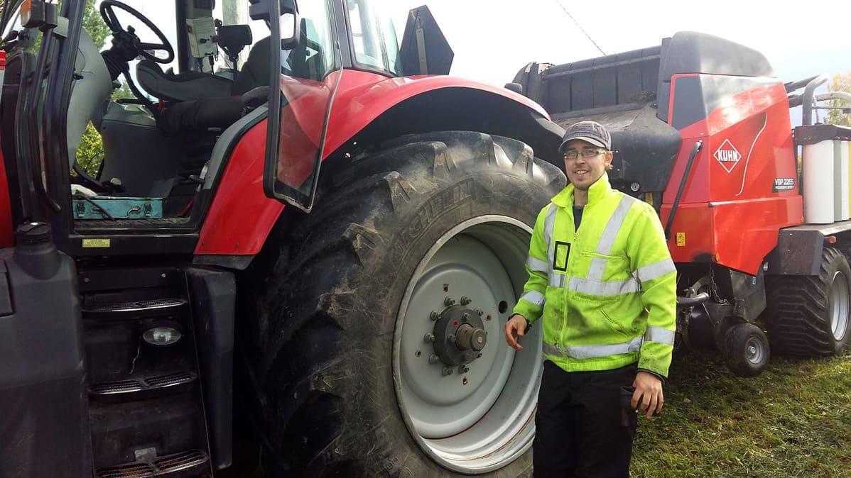 Viljelijä seisoo traktorinsa vieressä