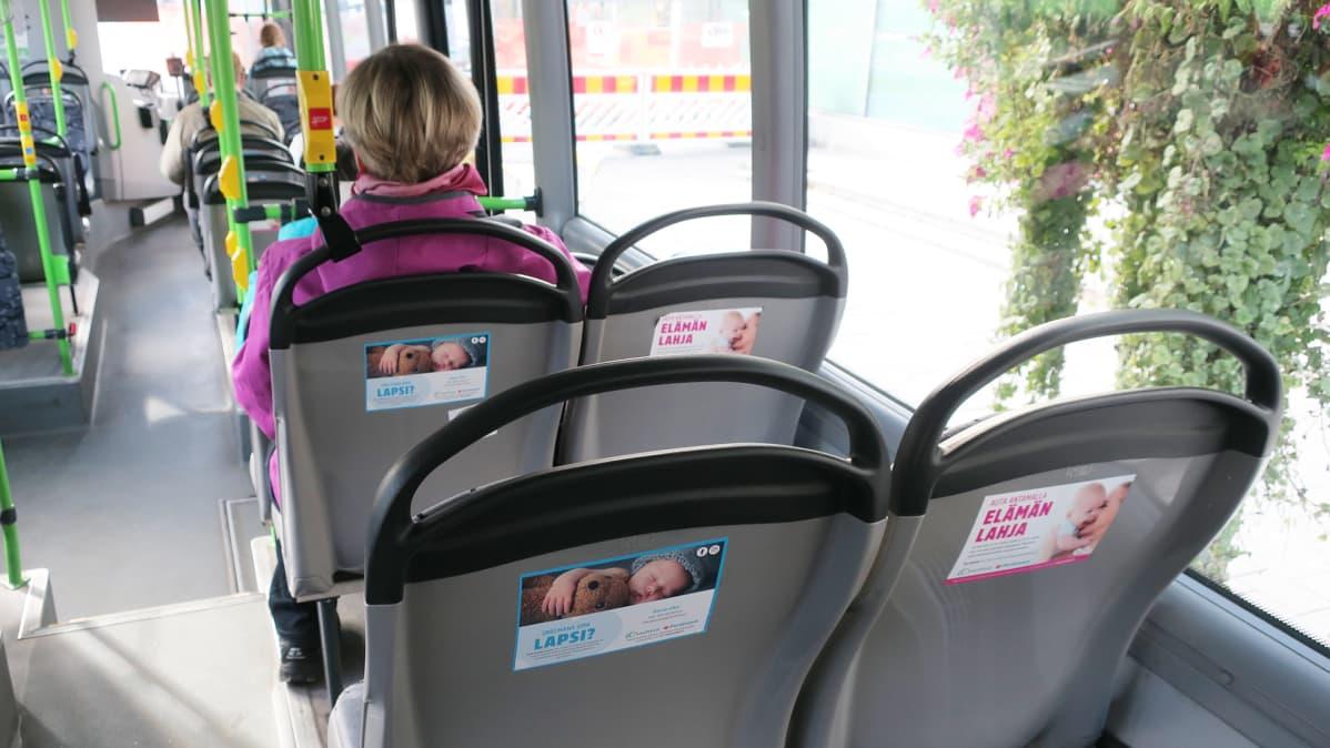 Ovumia Fertinovan mainoksia bussin penkkien selkänojissa.