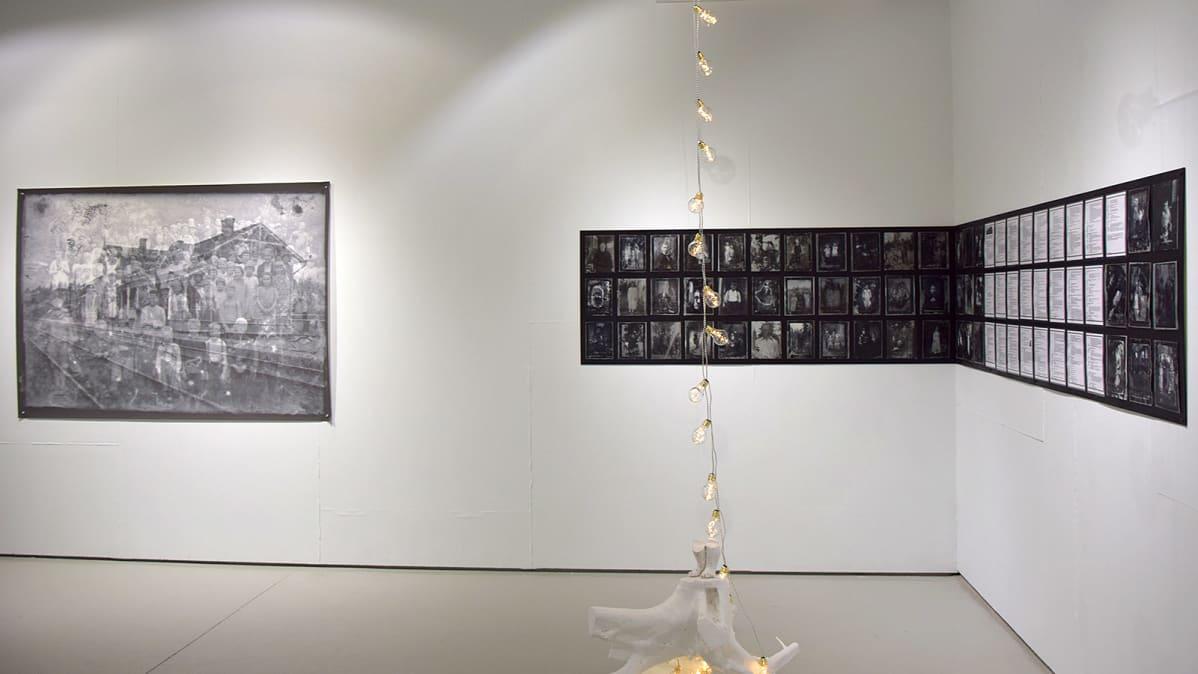 Vanhoja mustavalkoisia valokuvia kahdessa taideteoksessa, jotka ovat gallerian seinällä