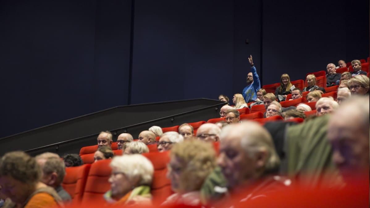 Mies viittaa yleisössä Finnpulpin tiedotustilaisuudessa.