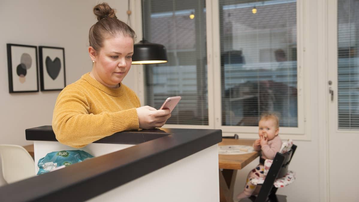 Äiti katsoo älypuhelinta ja vauva istuu syöttötuolissa taka-alalla.