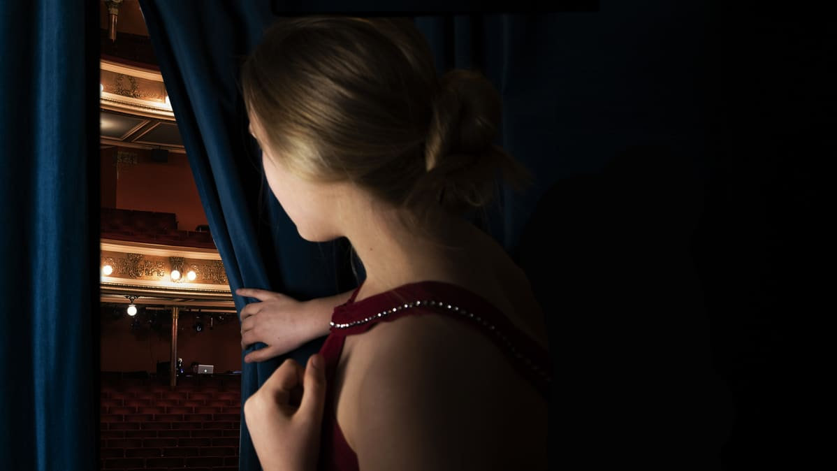 Laulaja kurkistaa verhon takaa katsomoon.