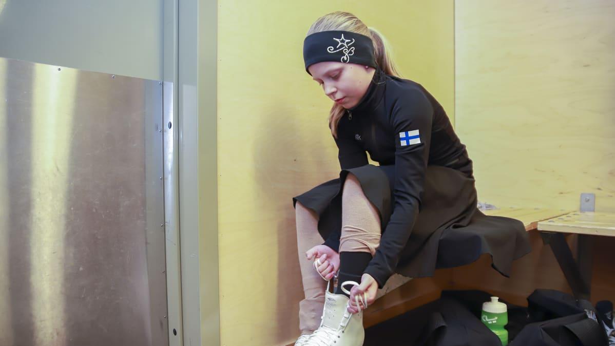 Tyttö laittaa luistimia jalkaan