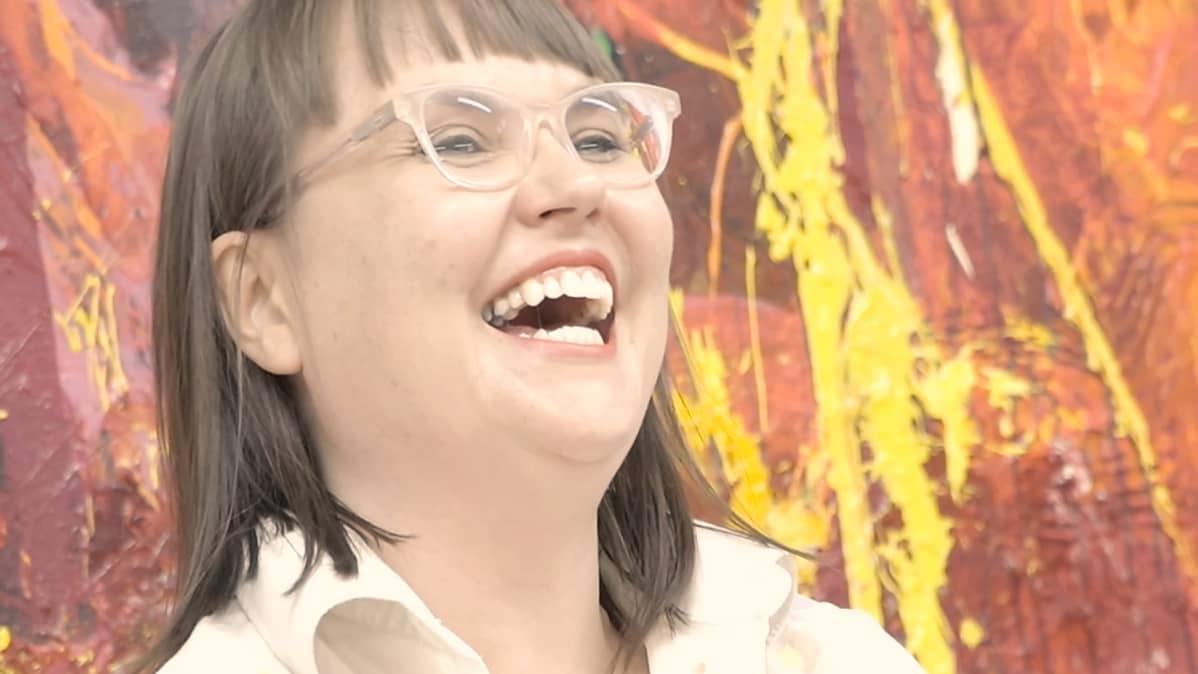 Maaria OIkarinen nauraa maalatessaan.