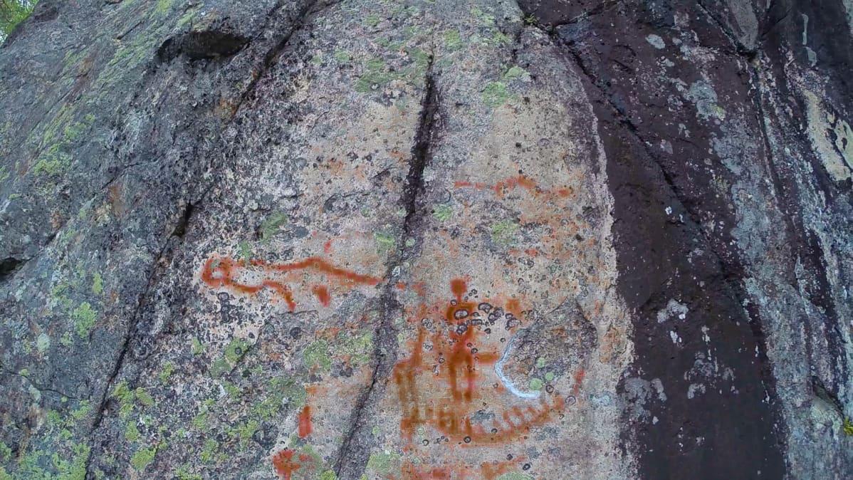 Kalliomaalaus, jossa kenties ihminen, vene ja hirvi.