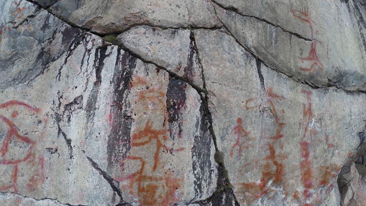 Yleiskuva kalliosta, jonka pinnalla monenlaisia kuvia.