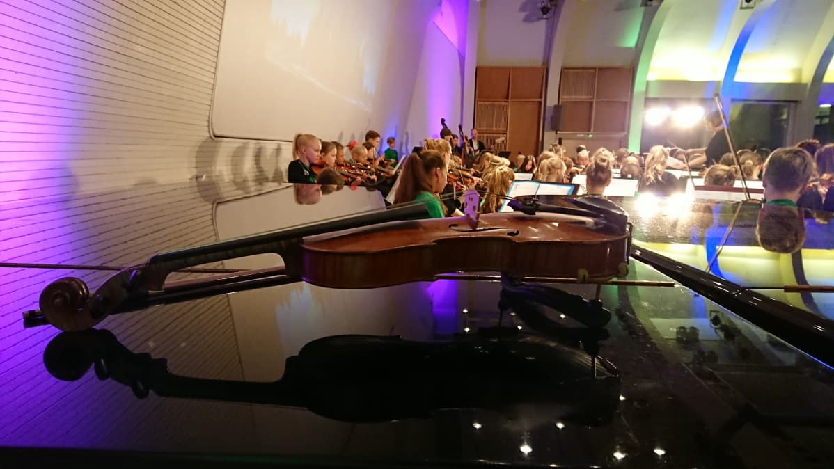 Kuvan etualalla viulu lepää pianon päällä, taustalla Joensuun konservatorion jousiorkesteri.