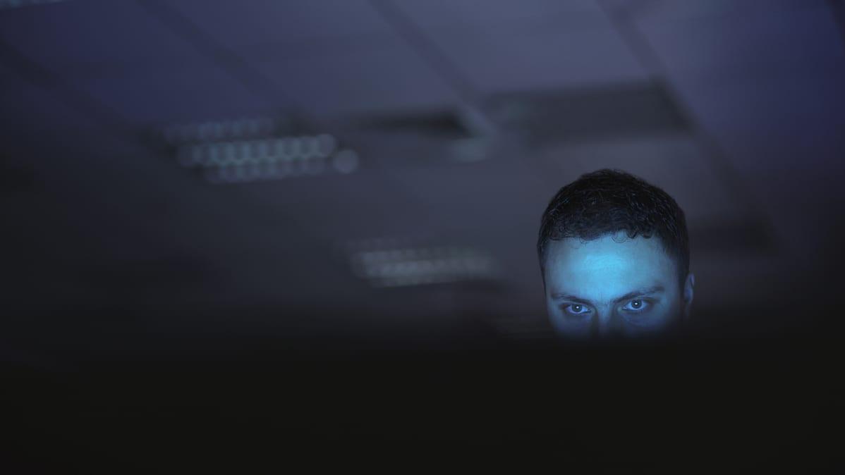 Mies tuijottaa tiiviisti tietokoneen ruutua hämärässä huoneessa.