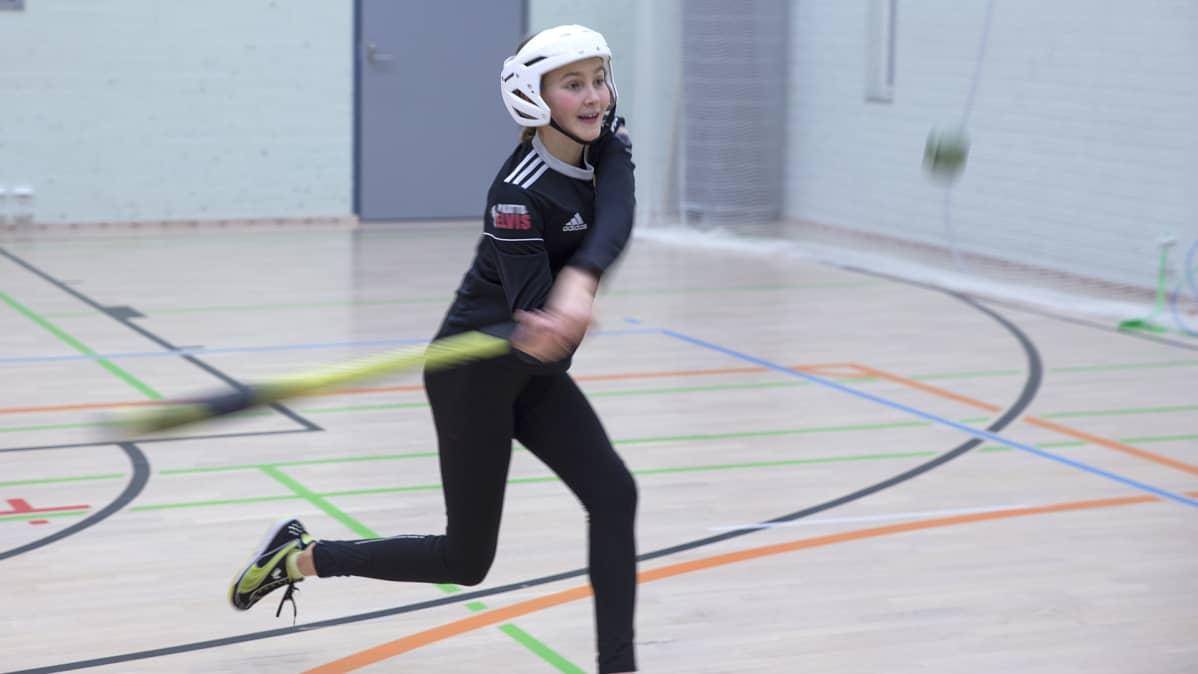 Sara Hyötyläinen pelaa pesäpalloa Ahmon koulun liikuntasalissa.
