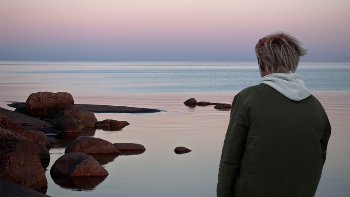 Mies meren rannalla.