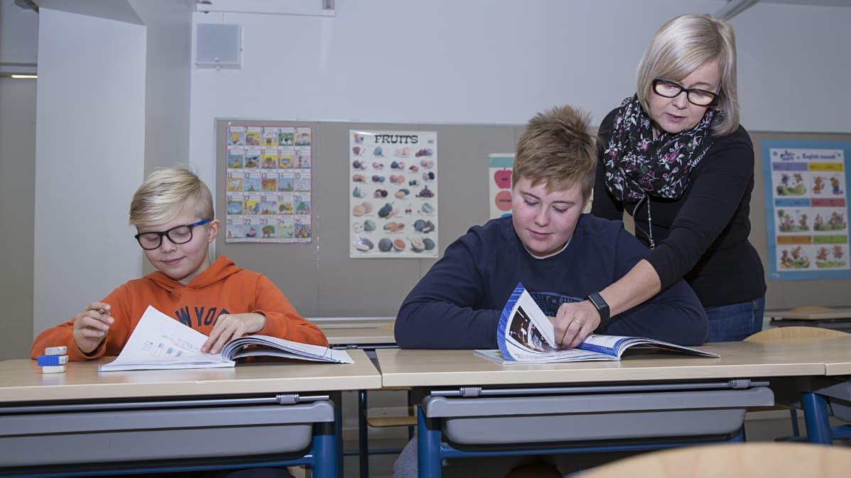 Opettaja opastaa koululaisia luokassa.
