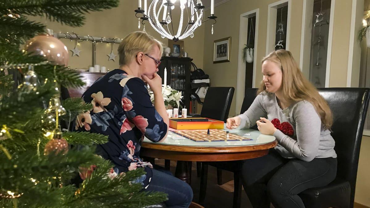 Katja Korpela ja Heidi Lindholm pelaa lautapeliä