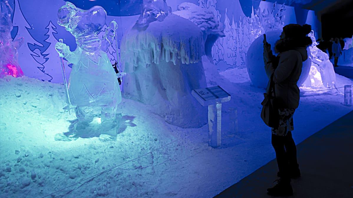 Nainen ottaa kuvaa muumi-jääveistoksista