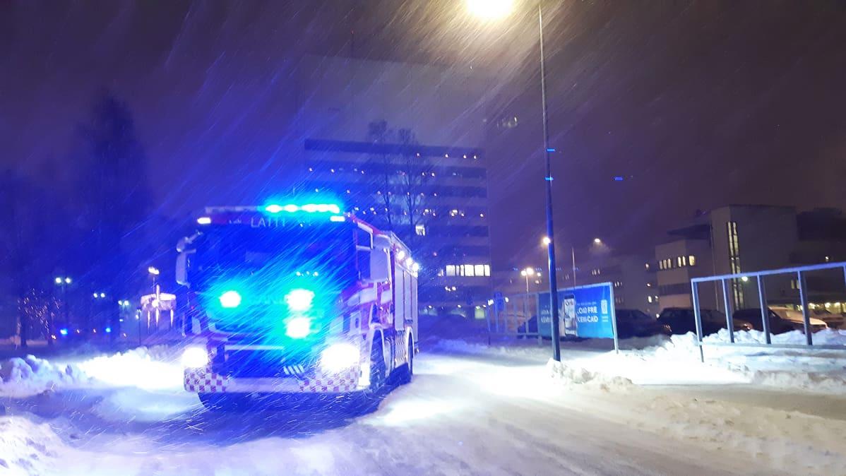 Pelastuslaitoksen paloauto kaupungin keskustassa kovassa tuulessa.